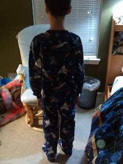 Muffin Man, with his back to the camera, wearing footie pajamas with rockets on them