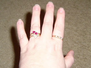 A picture of my hand with the rings on it. The engagement ring and chevron ring on my ring finger and the hugs and kisses ring on my index finger.