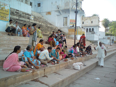 A group of pilgrims performing a puja assisted by a Panda at the Pushkar Lake