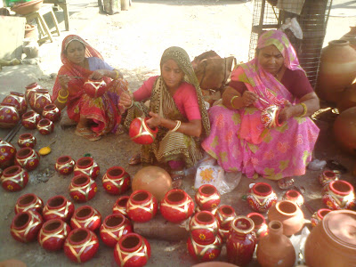 Women give finishing touches to the pots in Jaipur