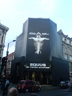 the facade of the Gieguld Theatre hidden by a giant poster for Equus