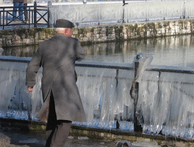 old man throwing stones on frozen lake