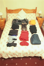 Rucksack and hiking gear arranged on bed