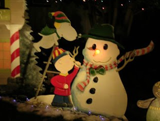 Snoopy putting the snowman's hat on his head.