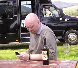 twitchhiker twittering at a Kunde picnic table. behind him is the California Wine Tours van.