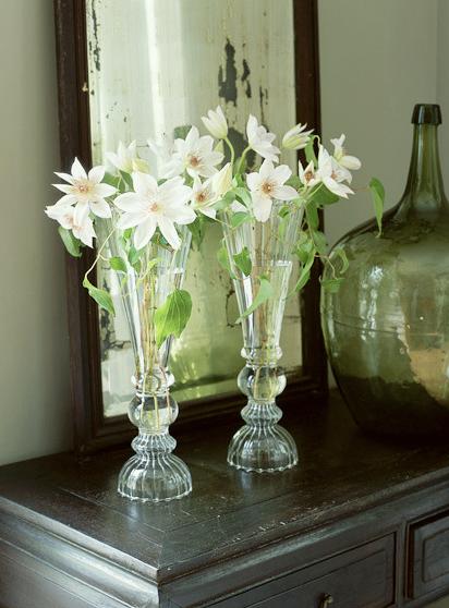 dos jarrones delgado y de delicado diseo del mismo tamao jugando con la simetria y la belleza de unas sencillas flores blancas
