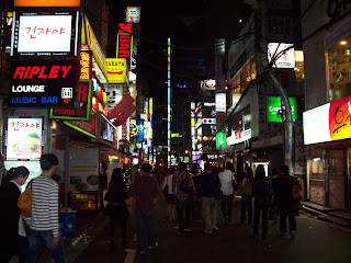 ELectric signs light up a streets scene with crowds in Gangnam