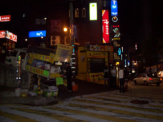 A cart vendor sells fruit and other items at night in Gangnam