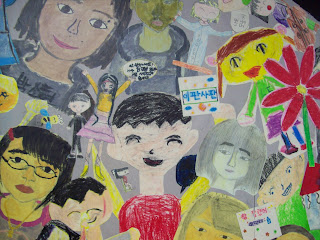 Clse-up shot of mural showing many differnet people, drawn by children