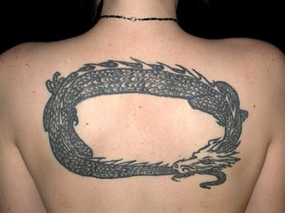 A man having beautiful arm dragon tattoo being pictured with his pregnant