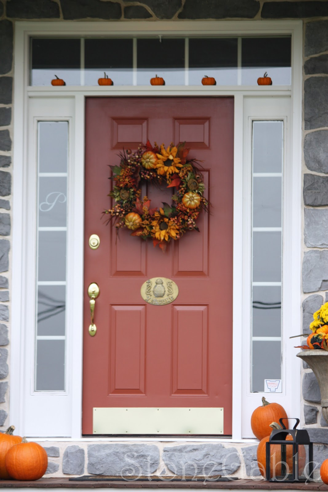 Outdoor fall decor stonegable bright yellow mums fill the urns that flank the front door pumpkin gourds and leaves fill in around the mums rubansaba