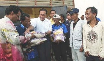 Welcome gift: Wan Rosdi (third from left) and Devamany distributing packs of rice to the orang asli at Pos Betau in Lipis recently