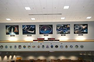 Por encima del reloj de cuenta regresiva, desde la izquierda y en el orden en que llegaron a Kennedy están los homenajes artísticos a Columbia, Challenger, Discovery, Atlantis y Endeavour