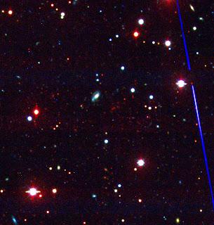 Esta imagen óptica del cúmulo de galaxias recién descubierto pone de relieve el enrojecimiento de estas galaxias debido a su gran distancia