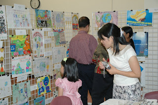 Award ceremony attendees admire posters submitted for the contest.