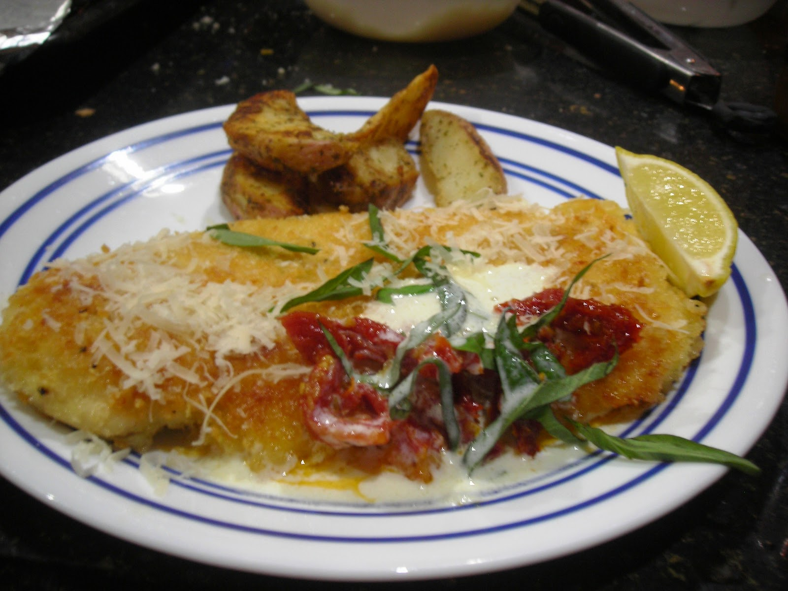 family cooking parmesan crusted chicken breast with lemon