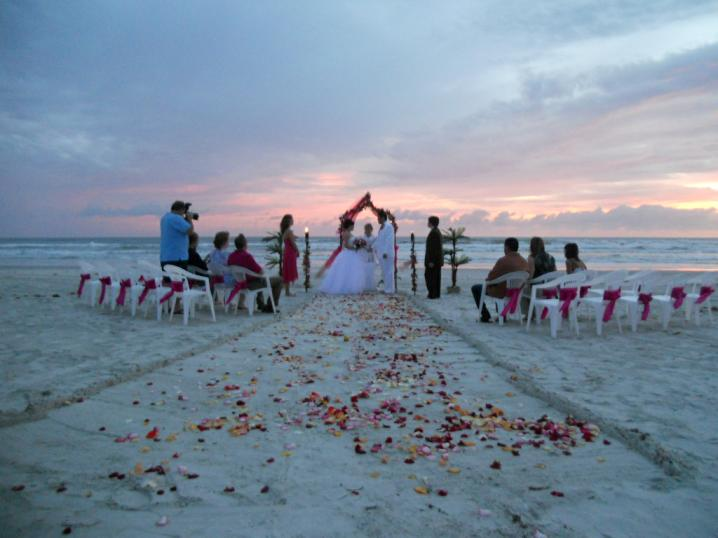 a beautiful white wedding arch decorated with tropical flowers and your