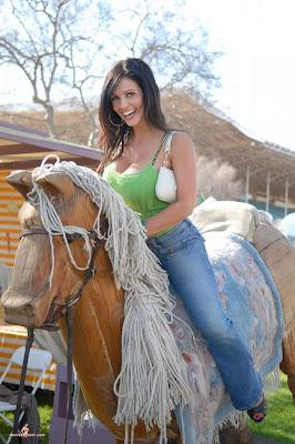 Denise Milani montana en un caballo de madera