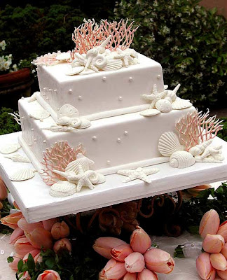 white wadding cake with shell and pearls