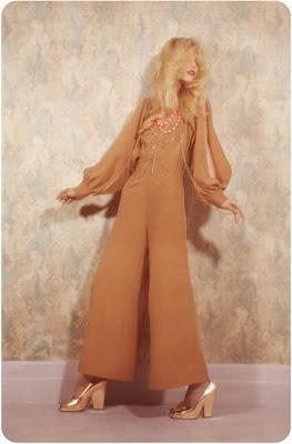 woman in 70's jumpsuit, gold shoes, farrawh fawcett hair, fashion shoot