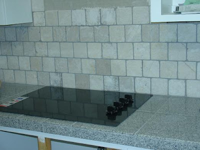 Tumbled marble backsplash reflected in a granite worktop Diagonal Tumbled Marble backsplash with tumbled marble