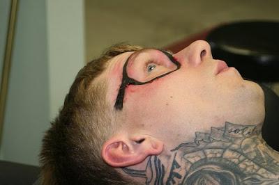 Mec qui se fait tatouer des lunettes