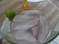 Cleaning the fish in water, lemon, and lime juice