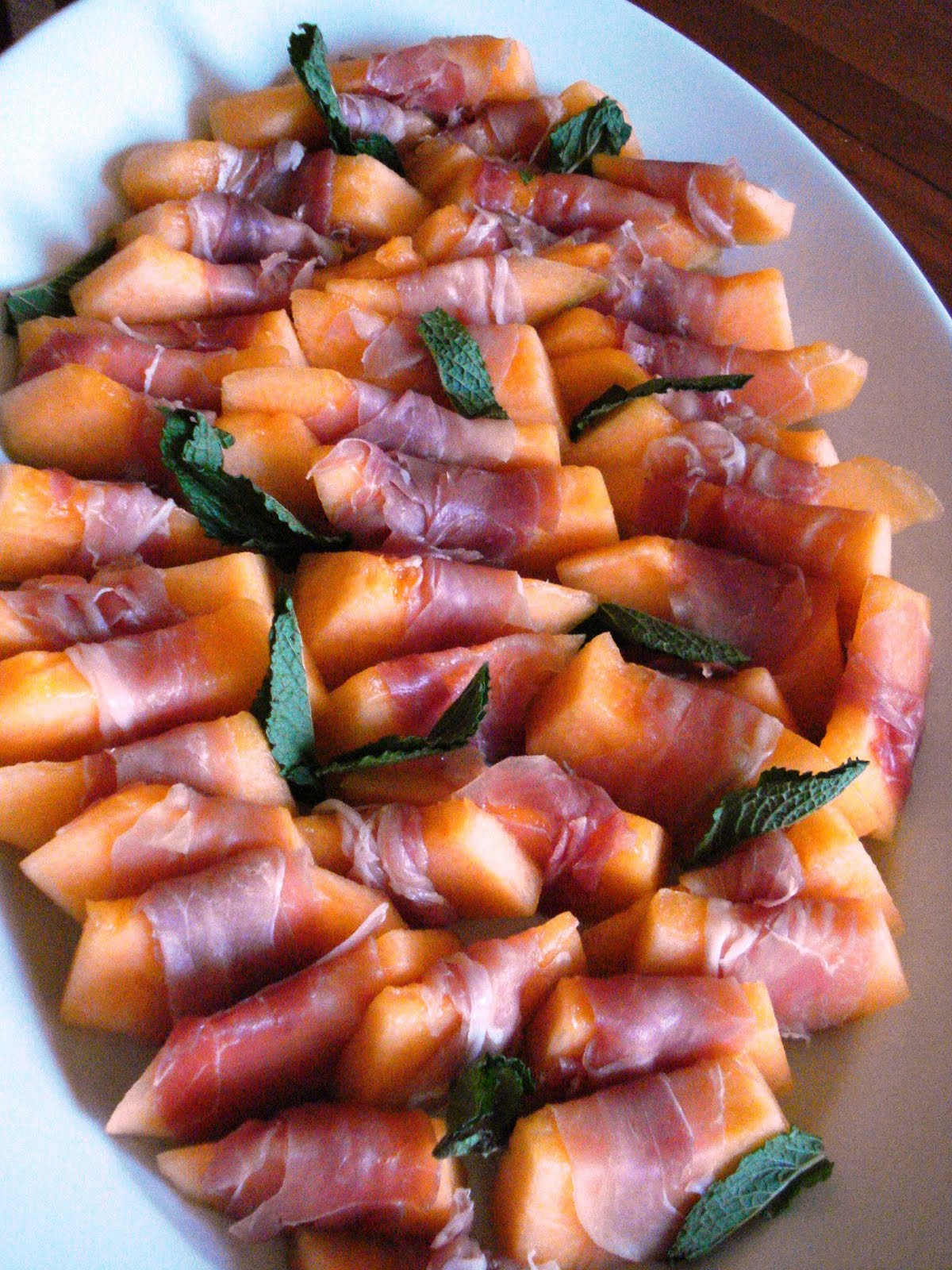 Cantaloupe melon wrapped in prosciutto with fresh mint