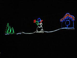 Снеговик спешит к себе в домик и несет новогднюю елочку