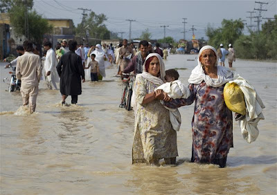 Women wade through flood waters with their children while evacuating from Nowshera, Pakistan.