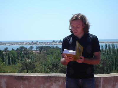Rui Andrade lendo 'O Meu Algarve' na açoteia do chalé, com a Ilha da Armona ao fundo