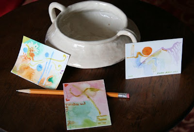 photo of three small paintings with a pencil and a bowl for size comparison