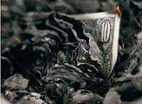 Photo of dark smoldering ash burning money