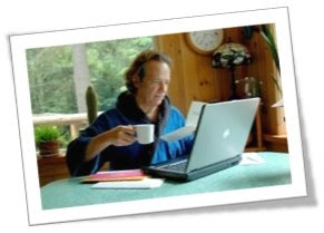 Photo of Bill sitting at his kitchen table paying bills and donating online with his computer