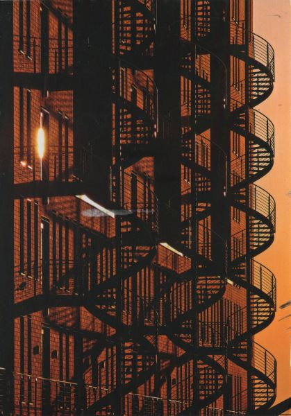 silhouettes of outside spiral staircases on a warehouse at sunset