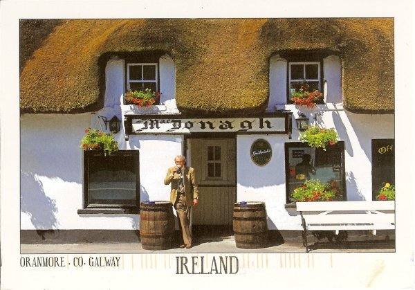 man leaning against Irish thatched pub