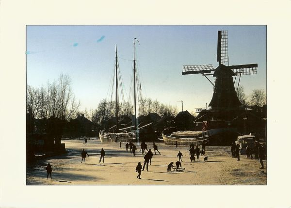 people skating and sledding on a frozen canal with windmill and barges