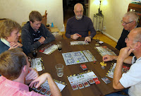 The players look at the RoboRally board, amazed at the chaos within a simple game