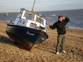 A boat and Richard Gottfried on a beach in Shoeburyness, Essex