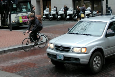 Bicyclist and car sharing the road