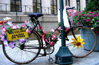 Image of flower decorated bicycle with bicycling against oil wars sign