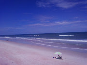 A lone figure under an umbrella on a mostly abandoned stretch of beach . (lonelyumbrellaman flaglerbeachfl pm sept )