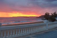 desde la terraza de la Playa de la Concha el cielo seguía ardiendo mientras el señor del detector de metales está a lo suyo