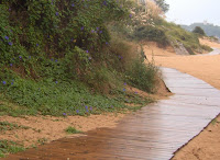 El camino que bordea la playa de los peligros con el Palacio de la Magdalena al fondo