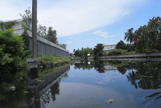 โรงงานเรียงรายริมคลองสนามชัย น้ำมีสีดำสนิทและมีกลิ่นเหม็นชวนเวียนหัว ส่วนล่างซ้ายมือของภาพเป็นคลองย่อยซึ่งนำพาน้ำเสียจากทั้งโรงงานและบ้านเรือนบริเวณอื่นๆ ไหลมารวมสู่คลองนี้