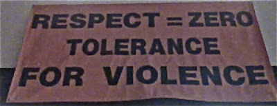 Ugly banner that reads Respect = Zero / Tolerance / for Violence