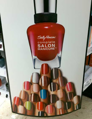 A pyramid of disembodied fingers each with a different colored nail, pointing up toward a red bottle of Sally Hanson nail polish