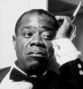 Louis Armstrong with cigarette in long holder, looking pensive