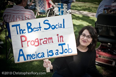 Smiling white woman with sign reading The best social program in Ameica is a job