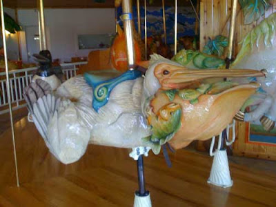 Colorful carved pellican on carousel